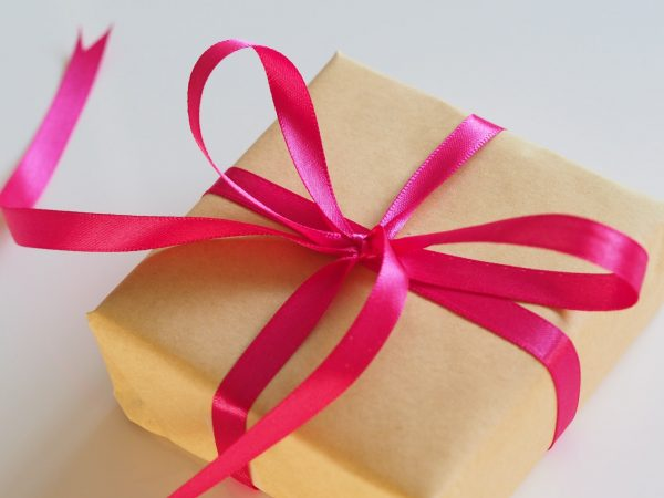 gifts for women, gold wrapping paper wrapped around a box with a pink ribbon bow.